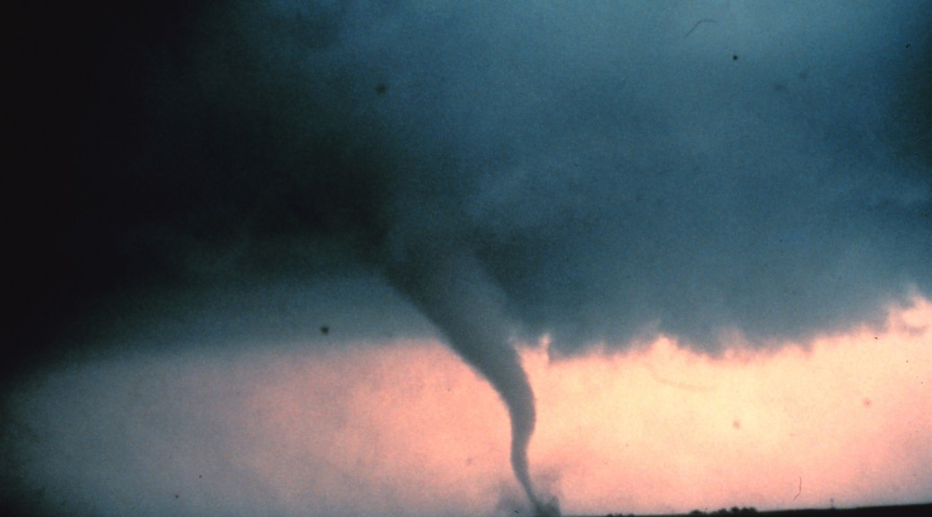Tornado with dust and debris cloud forming at surface.